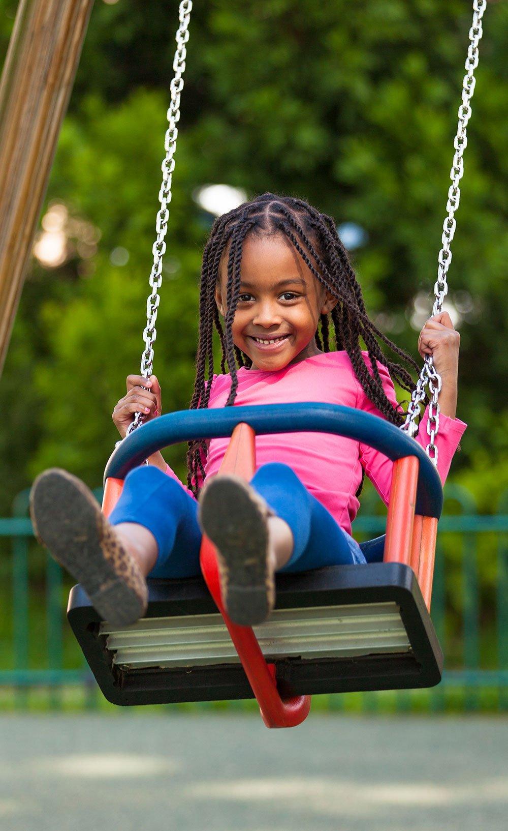 Girl on swing in a neighborhood park